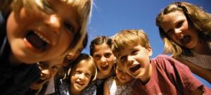 Ett gäng glada pojkar och flickor som gapar nedböjda mot kameran.